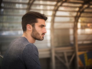 Handsome young man profile shot, indoor, inside big modern building, maybe a brand new train station, looking far