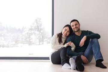 multiethnic couple sitting on the floor near window at home