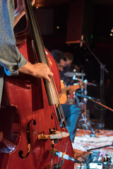 Acoustic trio band performing on a stage in a nightclub, with the double bass player in focus