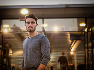 Handsome young man profile shot, indoor, inside big modern building, maybe a brand new train station, looking at camera