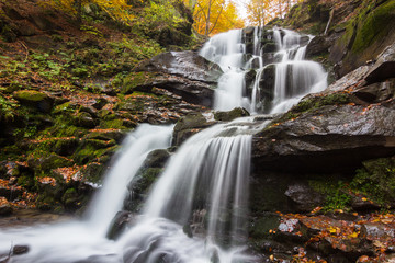 Autumn waterfall in forest landscape