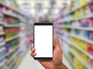 Man's hand holding blank white screen mobile phone on blurred supermarket background