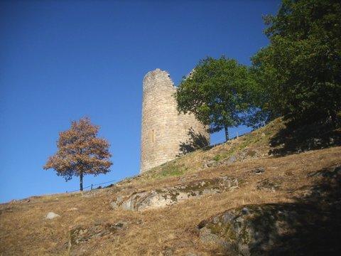 Paysage lumineux d'une ancienne tour de forteresse dressée entre deux arbres, sur les hauteurs d'un éperon rocheux. Ciel bleu pur en fond. Château de Crozant, La Creuse, Nouvelle-aquitaine. Eté 2016