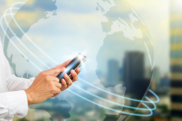 Hand holding smartphone on blurred globe and city background, communication technology concept