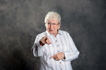 gray hairy elderly woman pointing in to the camera