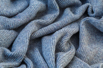 background of knitted gray linen of goat's wool made with knitting needles or on a knitting machine laid in waves.