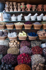 Colorful spices nuts dried flowers and pestle for cooking at open air spice market