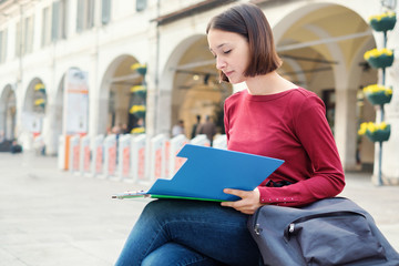 Female student with books and school bag in the city