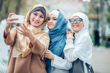 Three muslim woman laughing and making selfie together