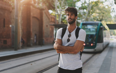 Portrait of a bearded man wearing casual clothes is waiting for the tramway on a street tram stop. Tourist guy exploring new city by a public transport on a summer vacation. Flare light.