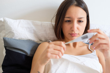 Woman feeling sick and watching the thermometer