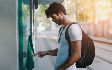 Bearded handsome hipster guy wearing casual clothes with backpack is buying bus tickets at self service vending machine on the station during vacation trip to European city. Flare light.