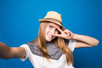 Trendy beautiful hipster girl taking selfie with victory sign on mobile phone against a blue wall.