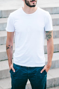 Young man wearing white blank t-shirt, standing on the street. Street photo. No face