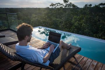Jeune homme travaillant près de la piscine