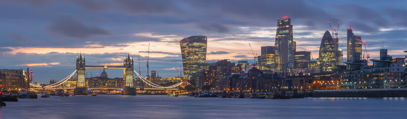 London - The panorama of the Tower bridge, riverside and skyscrapers at dusk with the dramatic clouds.