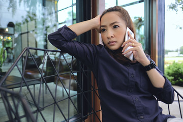 Businesswoman sit alone by talking mobile serious in case down sales target in project big