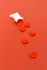 Close-up of a small shiny silver bag filled with cute red velvet hearts on red background. Concept of a romantic love gift for couples, valentines day, marriages or birthdays.