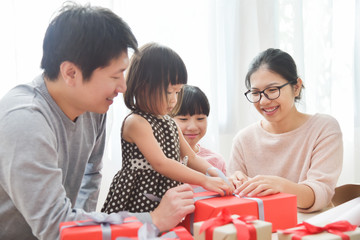 Happy Asian family wrapping a gift box.