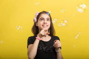 little girl playing with soap bubbles on white background