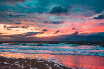 colorful clouds reflecting off the water as waves crash on shore and the sun rises on the horizon