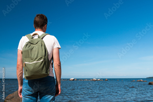 A tourist guy with a backpack on the Baltic Sea coast near Tallinn enjoys  nature in Estonia. Travel 009d205b7f3ac
