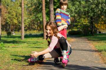 A little boy raises his sister who fell on roller skates. The boy helps the girl who fell, rolling on rollers in a park.