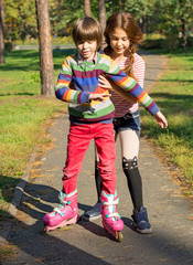 The girl helps the boy to roller-skate.