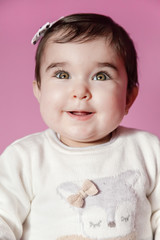 Cute, pretty and happy baby girl smiling portrait wearing a bow in hair. Nine months old