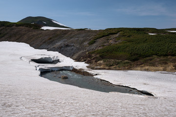 Bright white glacier on the slopes of mount Kurodake with a river running underneath, Daisetsuzan National Park, Hokkaido, Japan