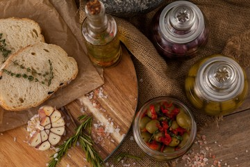 Olives in glass jars with ingredients and bread on table