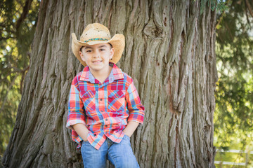 Mixed Race Young Boy Wearing Cowboy Hat Standing Outdoors.