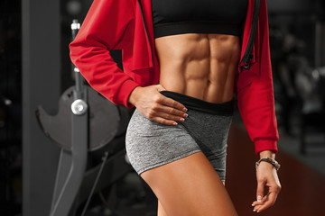 Fitness sexy woman showing abs and flat belly in gym. Beautiful athletic girl, shaped abdominal, slim waist
