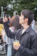 スマートフォンで写真を撮る男性