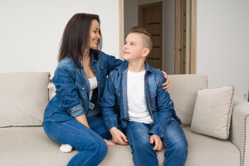 Portrait of mother and her son on sofa at home
