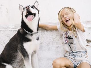 Beautiful blonde girl poses with pet Siberian Husky