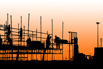 Silhouette of construction workers working on scaffolding with twilight sky