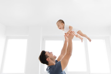 Young father throwing baby in the air