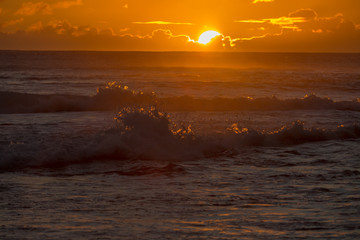 Sunset in the ocean, rough tropical water, splashing waves, warm colors