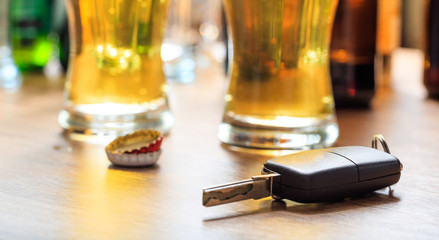 Drinking and driving. Car key on a wooden bar counter