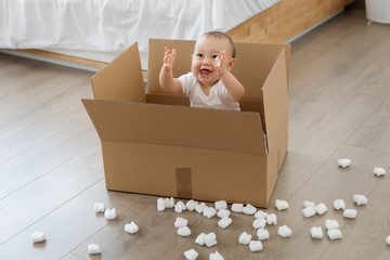 smiling baby sitting in cardboard box