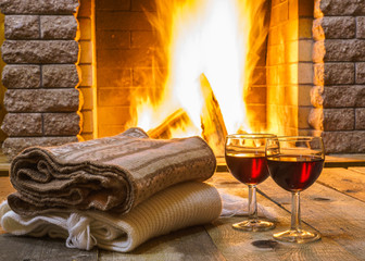 Two Glasses  of  red wine  and  woolen things near  cozy fireplace, in country house, winter vacation, horizontal.