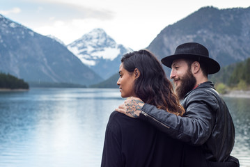 Hipster couple enjoys nature and scenic mountain lake in Austria