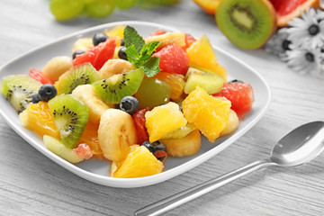 Plate with delicious fruit salad on wooden table