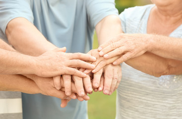Group of elderly people in park putting hands together as symbol of unity