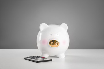 Cute piggy bank with calculator on table against grey background