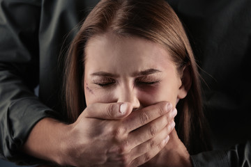 Man covering young woman's mouth