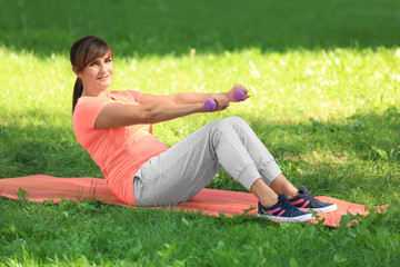 Mature woman doing exercises in park