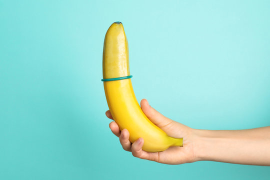 Woman holding banana with condom on color background