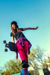 Cute urban girl holding skateboard in skatepark
